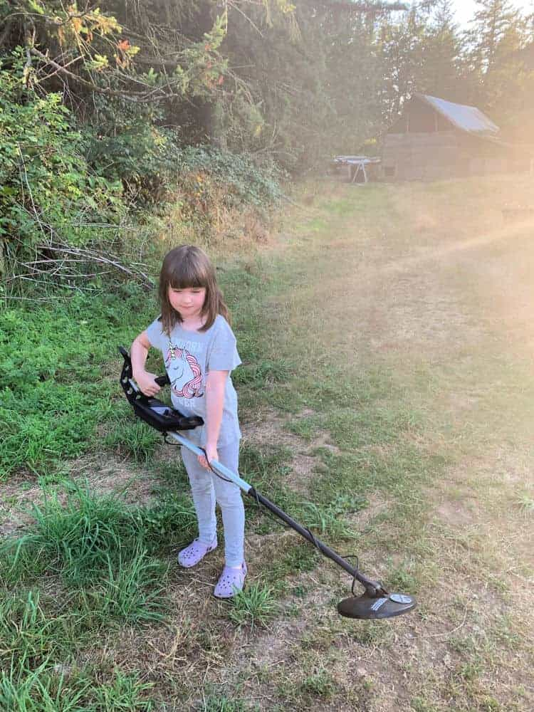 young girl holding metal detector in grassy field