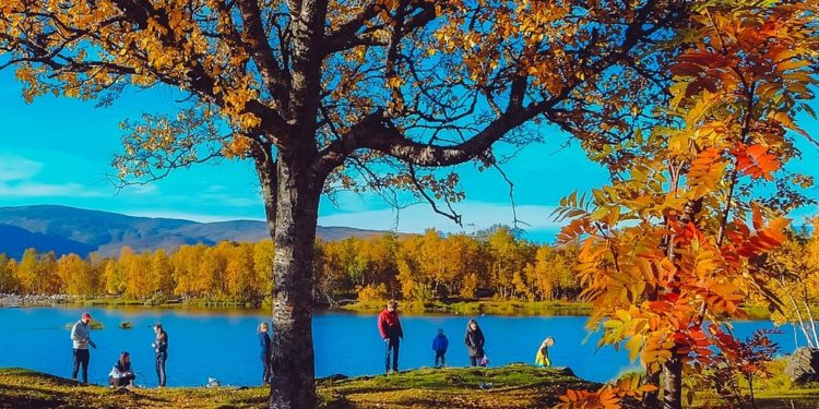 A family hikes along a lake in the fall.