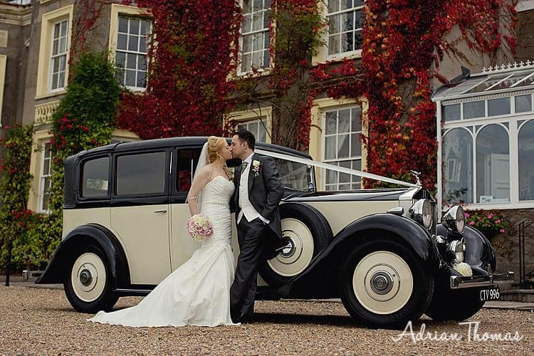 Bride and groom outside New House Country Hotel with wedding car