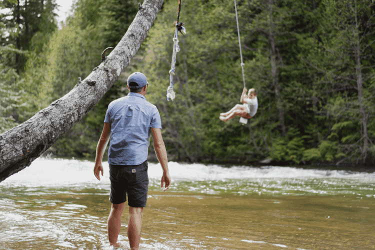 father pushing son on rope swing over river