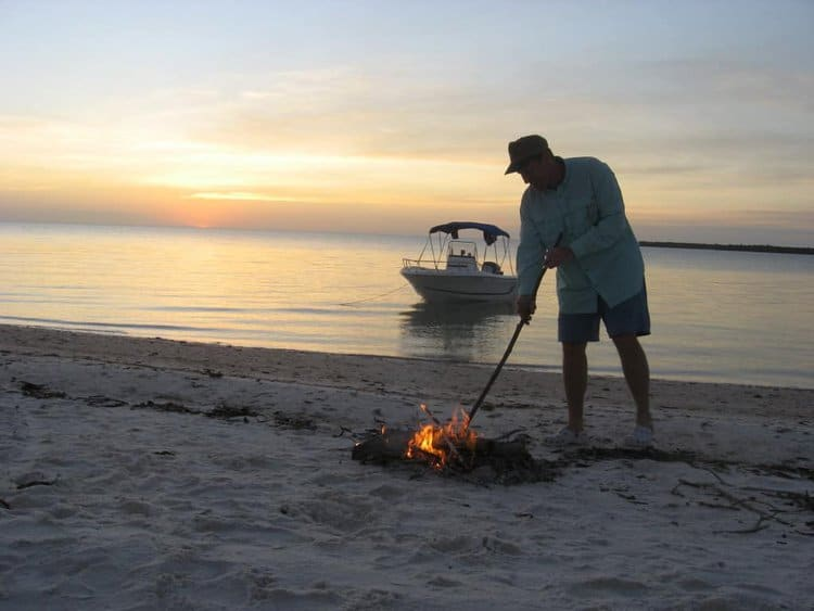 Warren stokes the campfire on the beach at Panther Key.