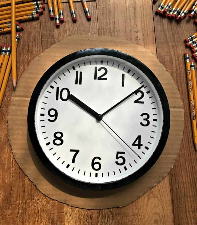 school clock on circle of cardboard with pencils around it