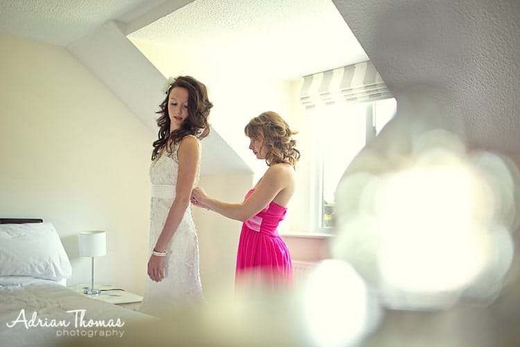 Image of Bride getting dressed during preperations at Llanerch Vineyard