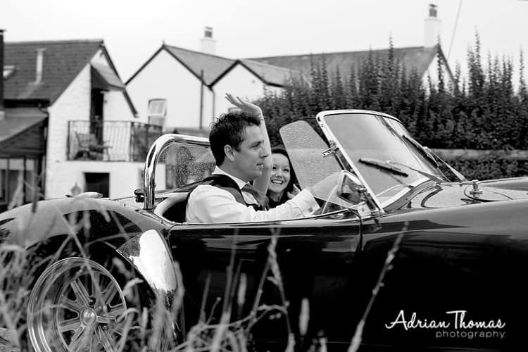 Photograph of wedding couple in car arriving at Llanerch Vineyard