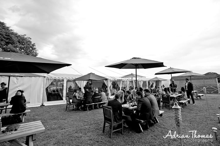 Photograph of guests chilling outside wedding marque at Llanerch Vineyard