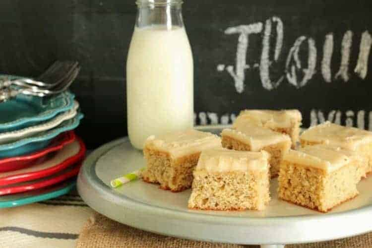 Banana Sheet Cake with Browned Butter Frosting cut in squares on serving tray with milk