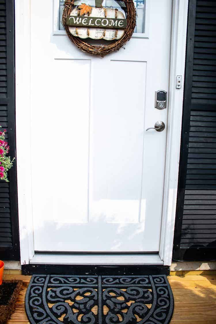 Front view of white door with autumn wreath and black doormat with Schlage Connect Smart Lock and Schlage Passage Lever in brushed nickel installed