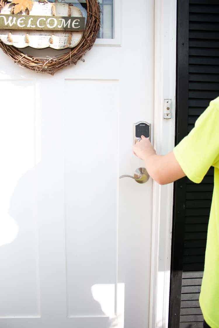 Boy opening Schlage Connect smart lock on front door