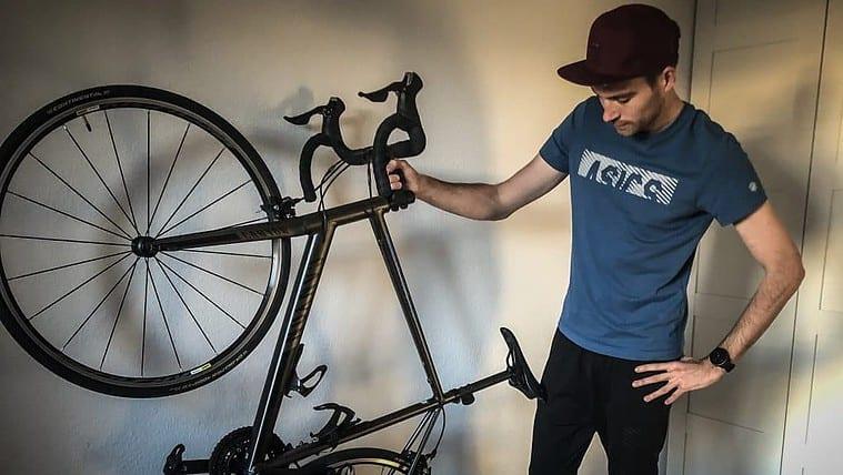 Sportler hält Fahrrad in der Hand