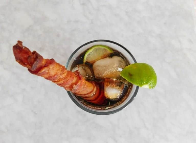 bacon straw in glass of rum and coke with a lime view looking down