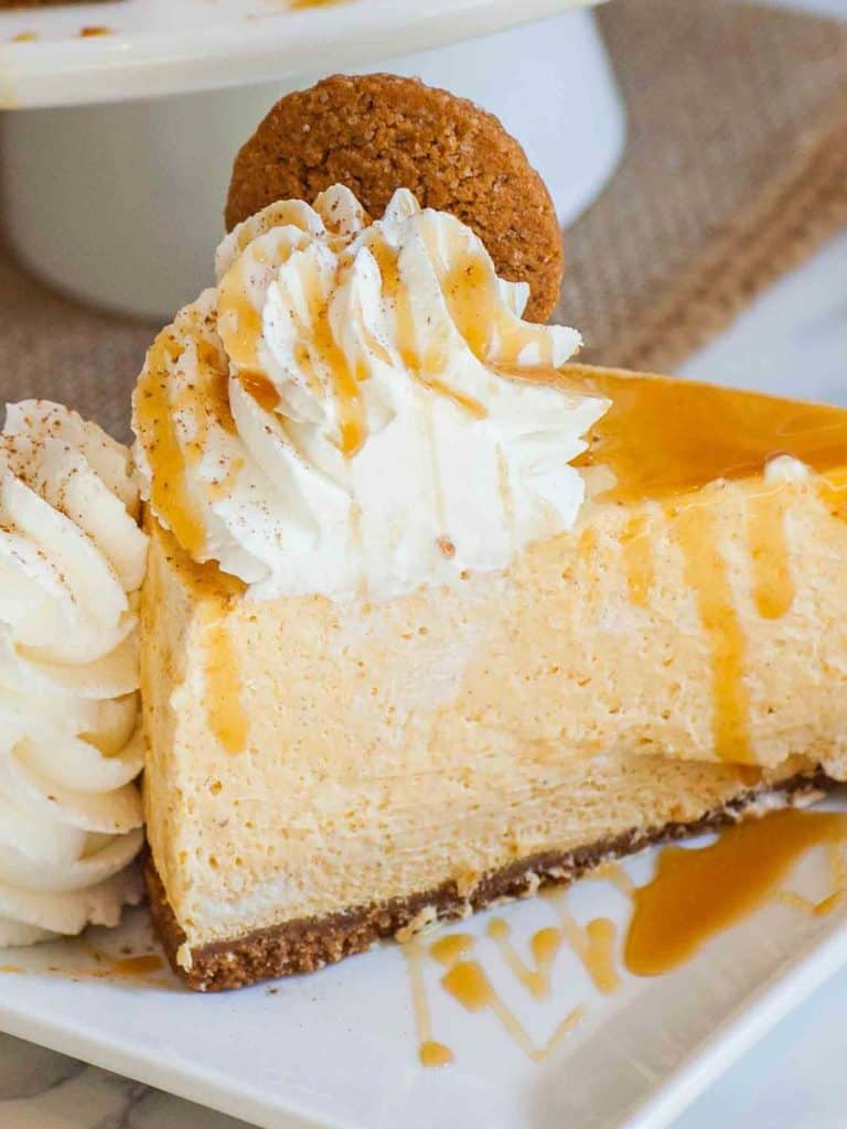 slice of pumpkin cheesecake with ginger snap cookies and cream