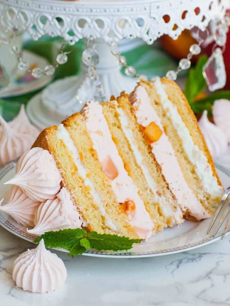 slice of peach cake with sponge cake and whipped cream
