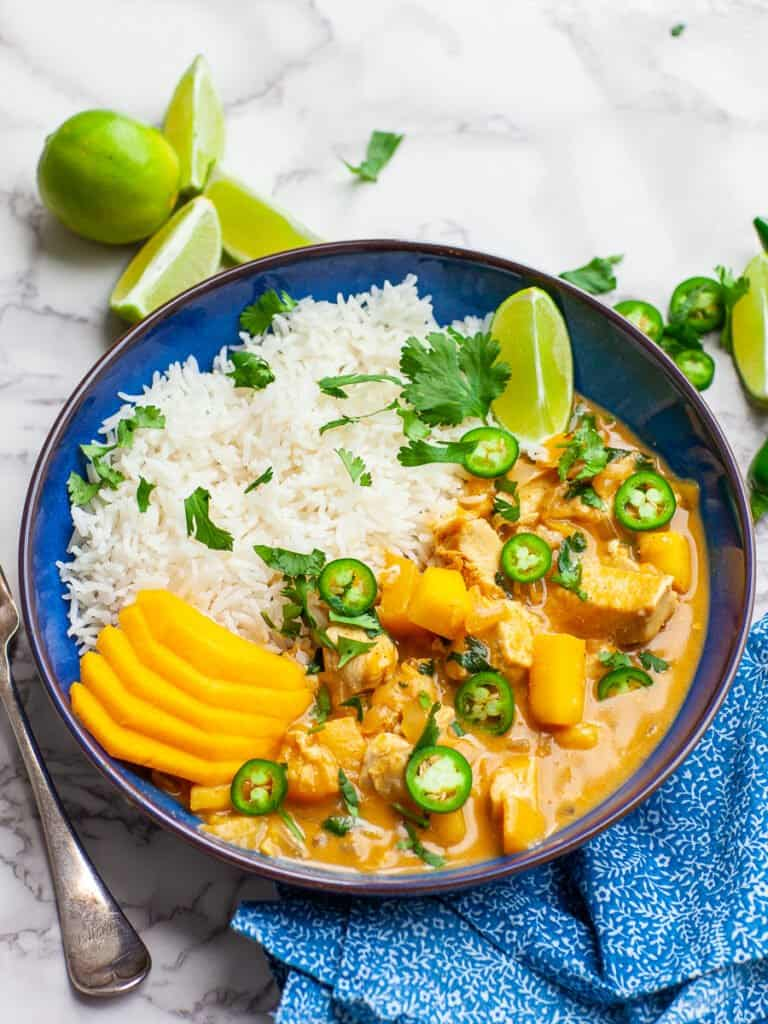 mango chicken curry with steam white rice, mango, limes and cilantro