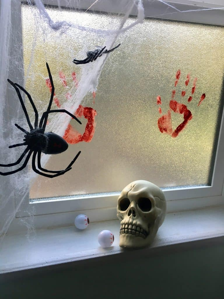 spider webs and bloody handprints are covering a window with a skull on the window sill.