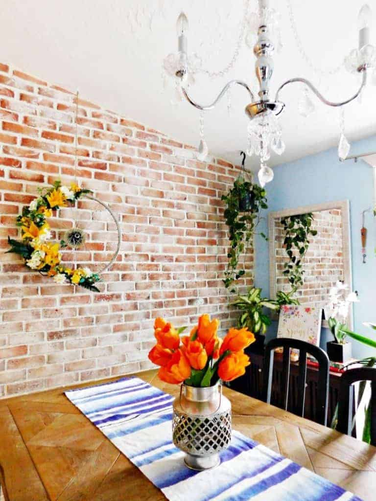 dining room with house plants. Brick wall with wreath and table with orange tulips