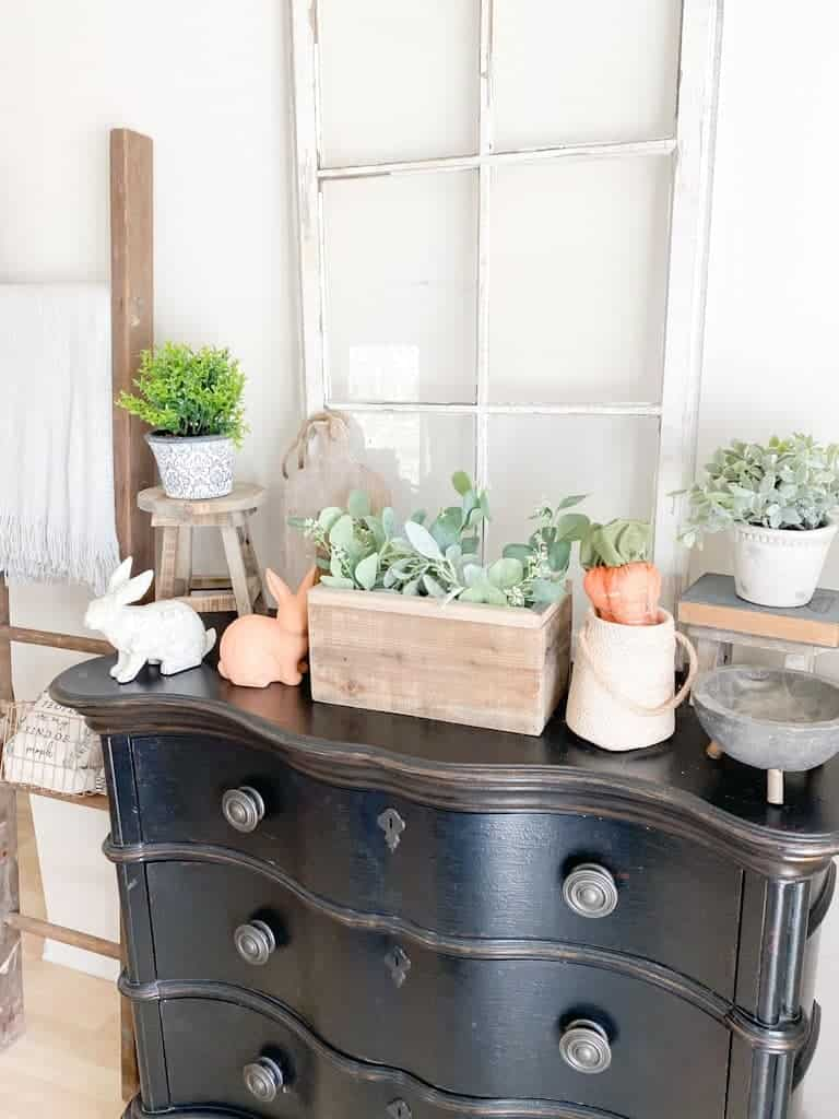 This image shows a black entryway table with an antique window, various spring decor, some small potted plants, and some wood decor items.