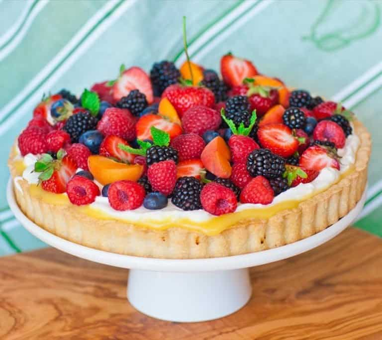 classic fruit tart with lemon curd, whipped cream and berries