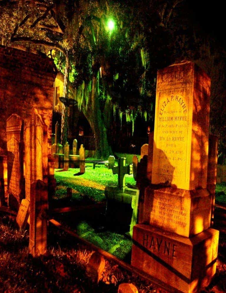 Spooky picture of cemetery lit up by a green light. Scariest Charleston ghost tour