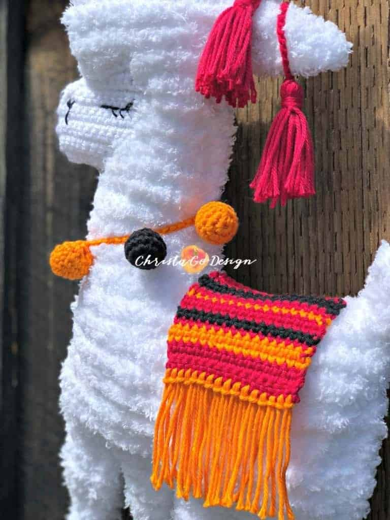 picture of fuzzy llama with orange and black baubles