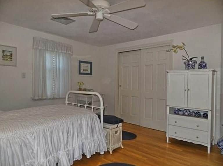 White is not always lighter and brighter, as seen in this dark and dingy bedroom