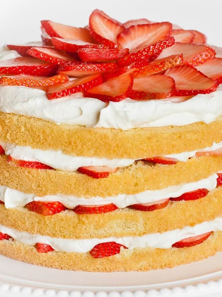 strawberry cake with sponge cake, whipped cream frosting and fresh strawberries