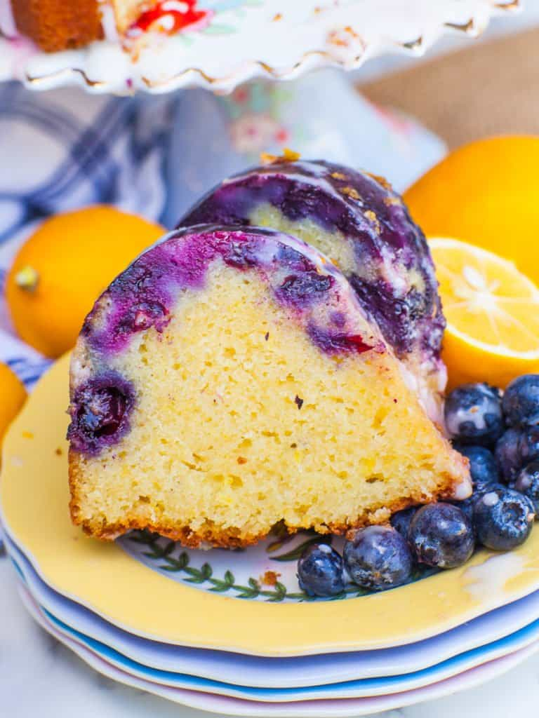 close up slice of blueberry lemon cake with lemon icing and fresh blueberries