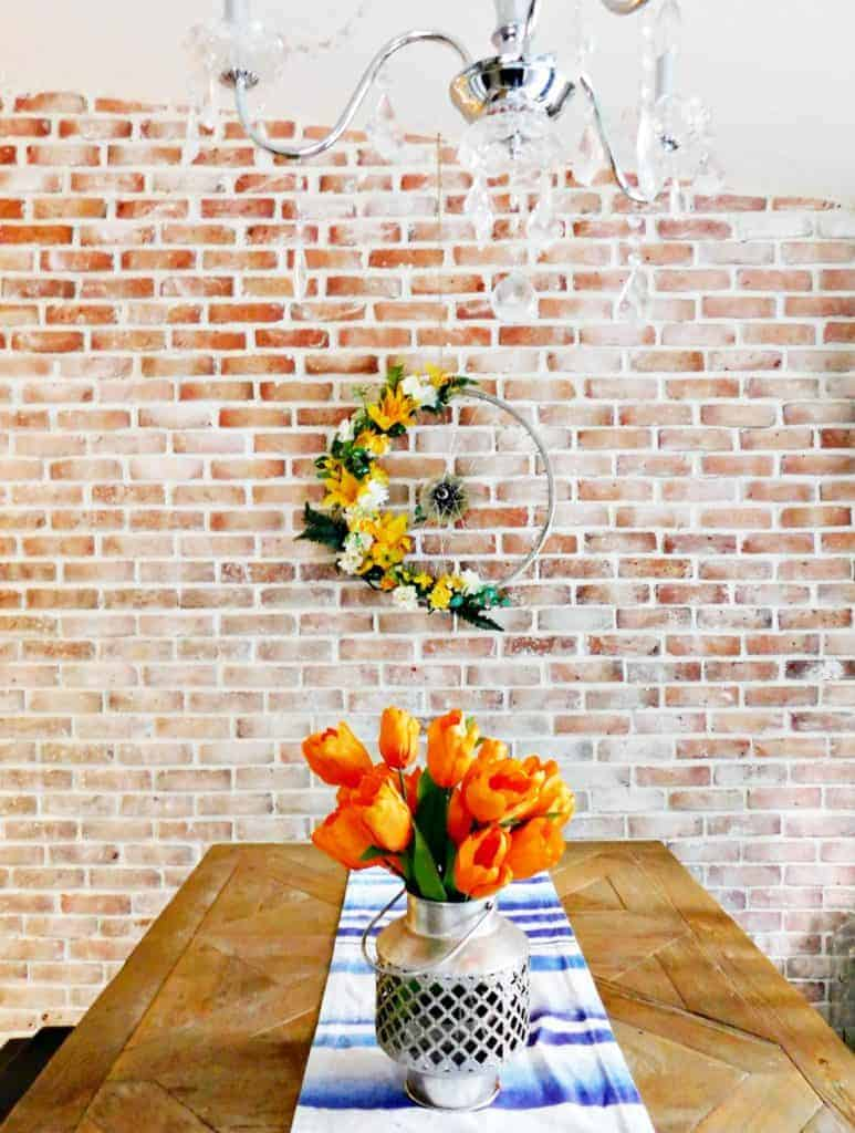 Bicycle Wheel Wreath yellow flowers on brick wall above dinner table