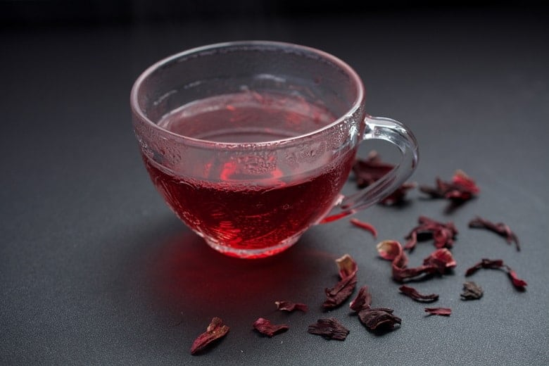 Red hibiscus tea in transparent cup on black table decorated with dried hibiscus petals