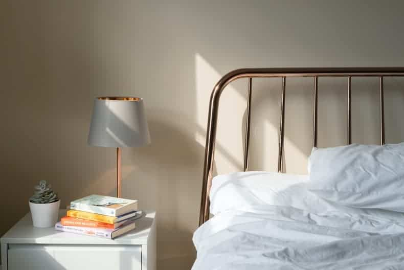 Bed frame with white bedding, a side table with lamp and books