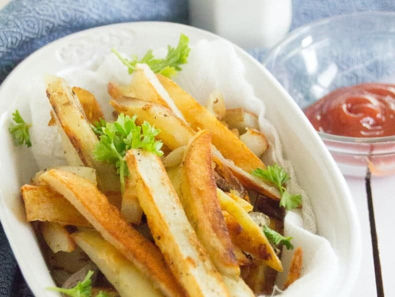 Homemade French Fries sit in a white ceramic bowl, on a blue tea towel on top of a white wood table top. A glass bowl of ketchup sits next to it. A white salt shaker, shakes salt above it.