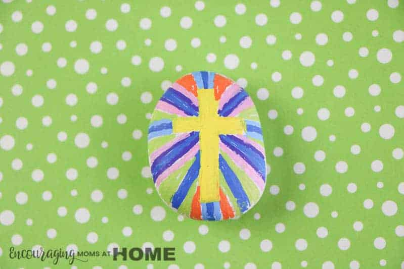 cross painted rock with yellow color on green background.