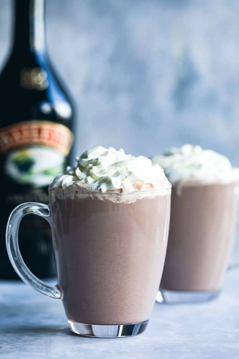 Two mugs of hot chocolate with squirty cream on top.