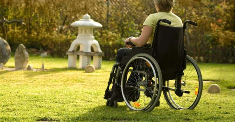 Disabled young woman in a wheelchair outdoors