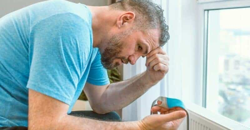man looking at CPAP medical device