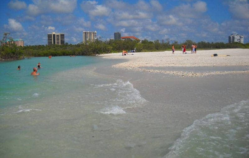 """Quiet beaches in Florida: The pass at Clam Pass is the river like body of water on the left. You can float in or out of the pass as the tide carries you on a """"lazy river"""" like ride."""