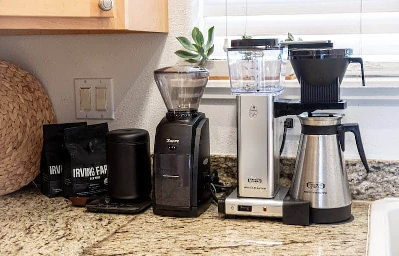 Baratza Encore and Technivorm Moccamaster on a counter with other coffee-making equipment
