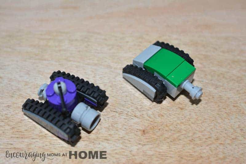 Two Lego Mini tanks face an unseen enemy. One is purple. The other is green.