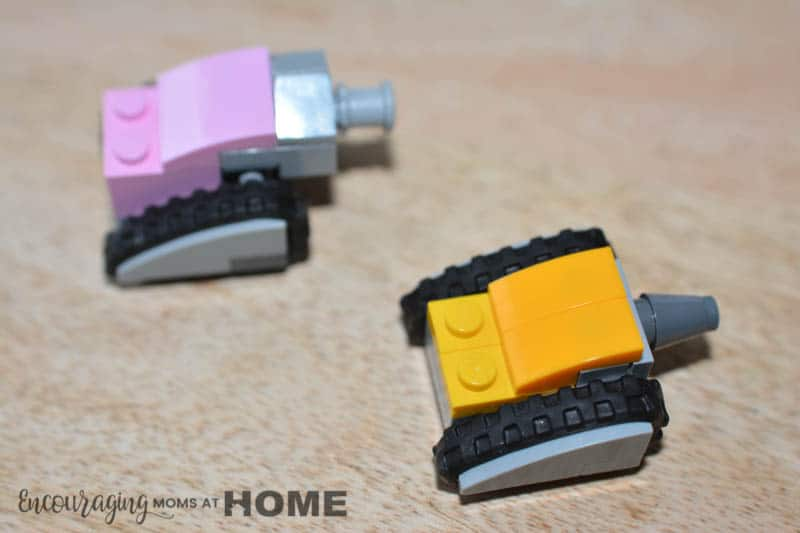Pink and Yellow mini Lego tanks face an imaginary opponent.