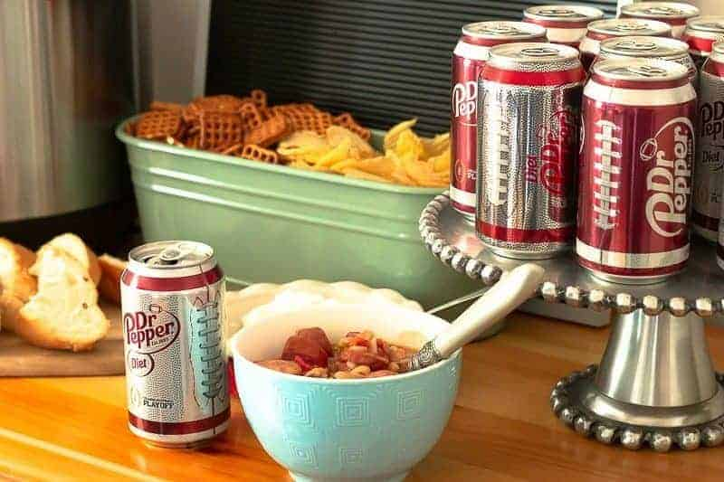 Homegating set up with Dr Pepper and homemade sausage and bean soup with rice in blue bowl