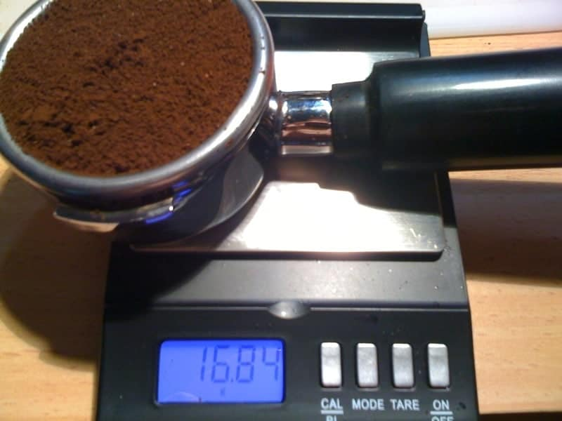 A portafilter containing coffee grounds on top of a kitchen scale