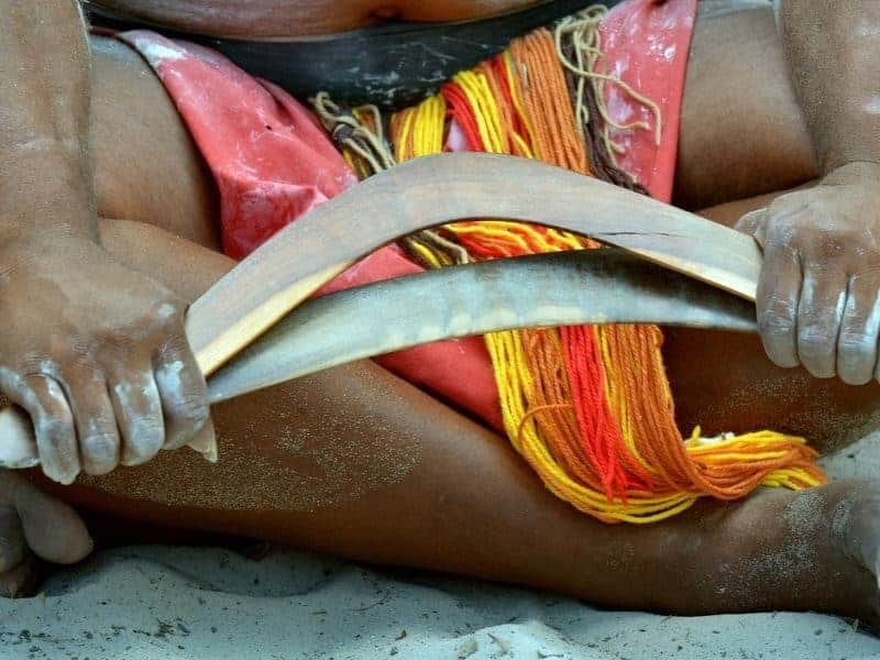 An aboriginal man making a traditional boomerang on a beach
