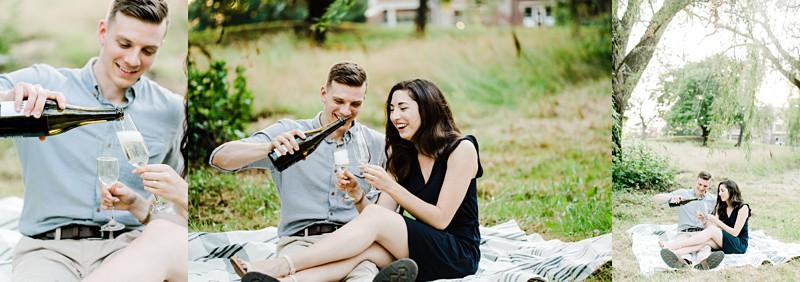 mayslake peabody estate engagement session couple sitting on the ground opening bottle of champagne