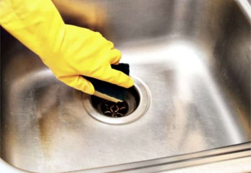 Homemade Soft Scrub Cleaner - Hand in rubber glove scouring stainless steel sink until it sparkles