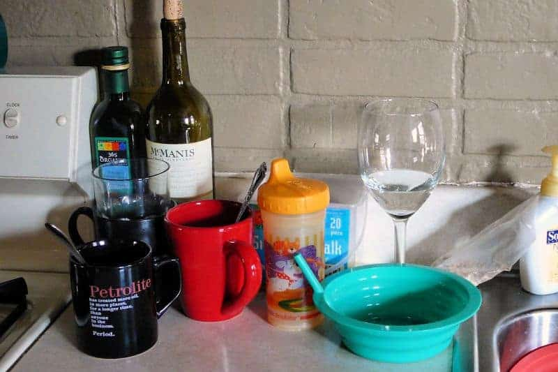 Dirty dishes and a wine bottle on kitchen counter