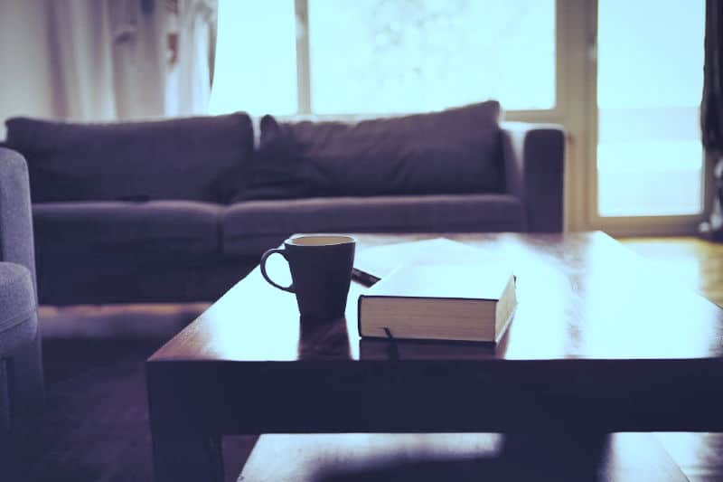 Polished wood coffee table with a book and coffee cup