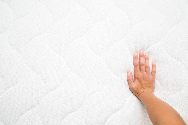 Hand on clean mattress with stains removed