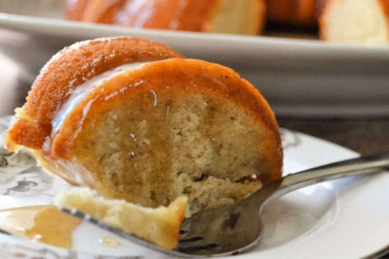 A slice of Banana Bundt Cake with Caramel Sauce dripping from it onto a white plate