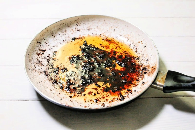 Overhead of burnt food on pan that needs to be cleaned