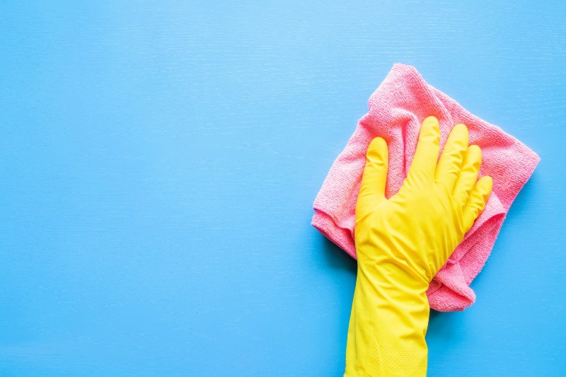 Hand in yellow rubber glove using a pink cloth to do the Daily Cleaning Routine