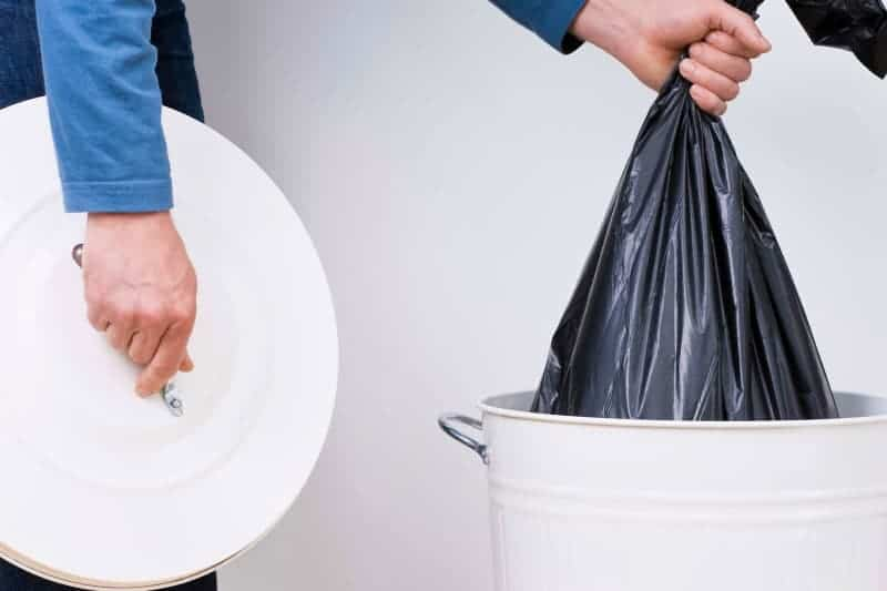 closeup of person removing full trash bag from garbage can while holding lid